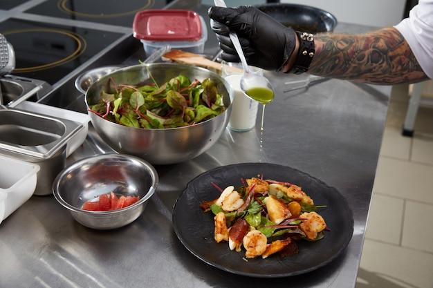 Primer plano de las manos del chef preparando ensalada de camarones en la cocina de un restaurante de lujo
