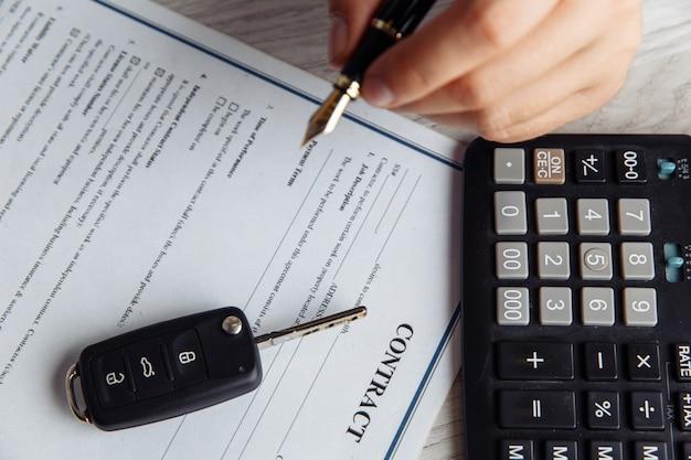 Primer plano de las manos del cliente que firma el formulario de arrendamiento del coche