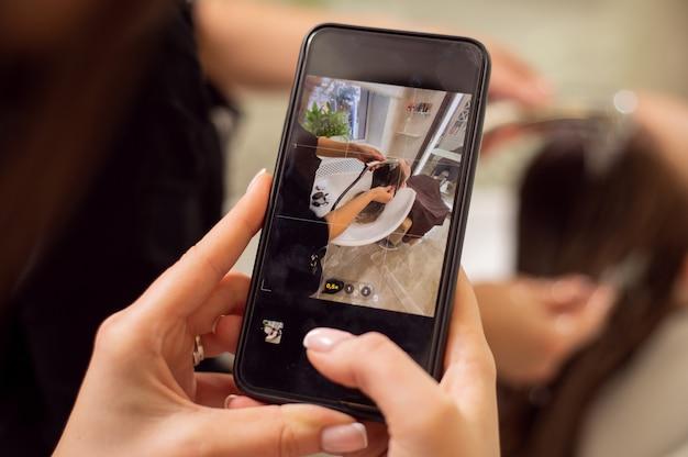 Primer plano de manos cuidadas sosteniendo un teléfono inteligente negro en modo de vista en vivo y tomando una foto de un lavado de cabello en un salón de belleza