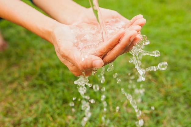 Primer plano de manos debajo de un chorro de agua