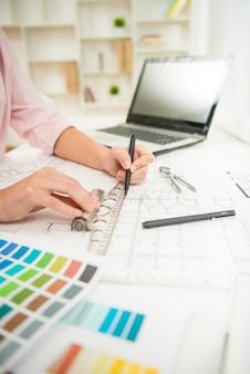 Primer plano de las manos del diseñador trabajando con el plan arquitectónico.