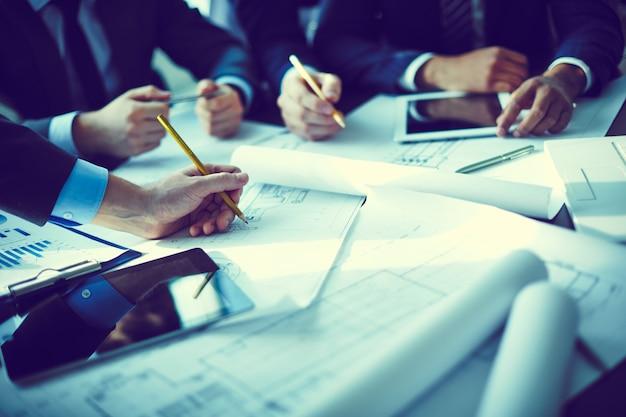 Primer plano de las manos de los ejecutivos enseñando el proyecto Foto gratis