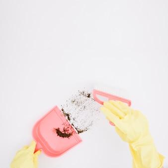 Primer plano de las manos enguantadas amarillas barriendo polvo en el recogedor sobre fondo blanco
