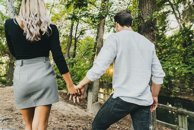 Primer plano de las manos entrelazadas de una pareja de enamorados caminando por un bosque.