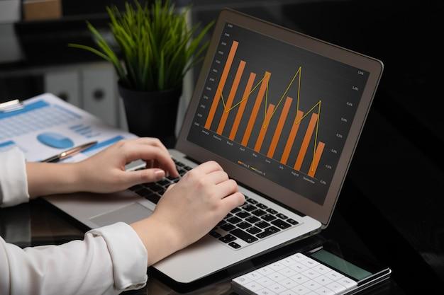 Primer plano de las manos escribiendo en la computadora portátil con pantalla negra en blanco junto a gráficos y calculadora