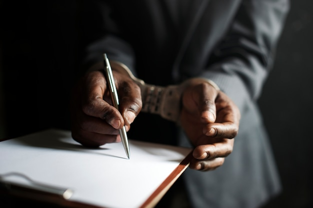 Primer plano de manos esposadas obligadas a firmar papel