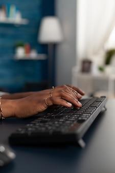 Primer plano de las manos del estudiante negro escribiendo información educativa en el teclado
