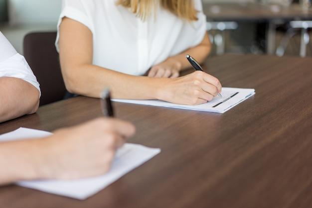 Primer plano de las manos de los estudiantes escribir el examen en los papeles.