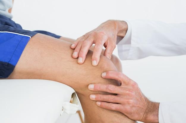 Primer plano de manos examinando pacientes rodilla