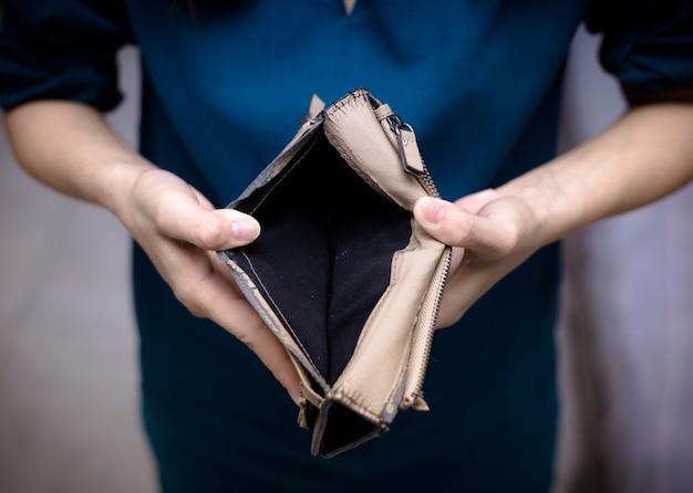 Primer plano de manos femeninas con una billetera vacía