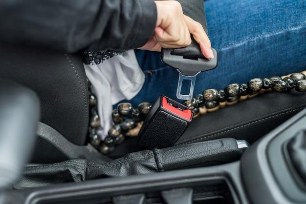 Primer plano de manos femeninas, cinturón de seguridad de sujeción