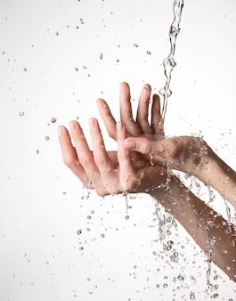 Primer plano de las manos femeninas bajo la corriente de salpicaduras de agua - concepto de cuidado de la piel