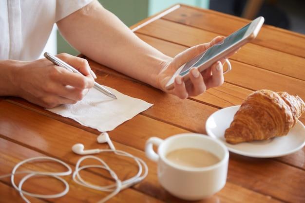 Primer plano de manos femeninas escribiendo una nota sobre la servilleta