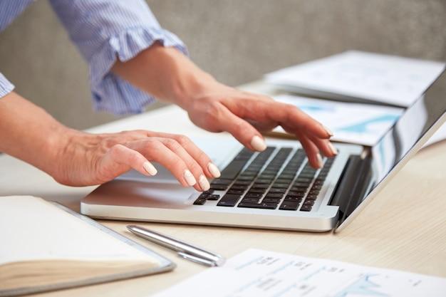 Primer plano de manos femeninas escribiendo en el teclado del ordenador portátil