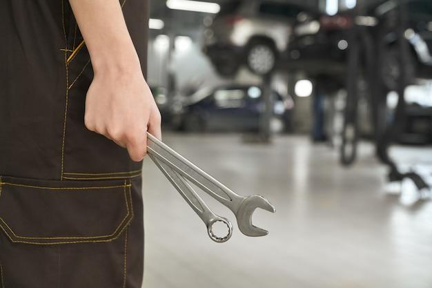 Primer plano de manos femeninas manteniendo llaves en taller