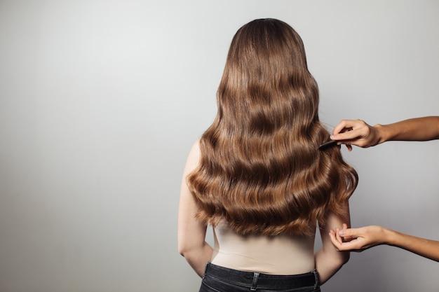Primer plano de manos femeninas de peluquería o peinado hace peinado. cabello