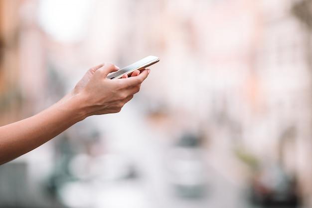 Primer plano de las manos femeninas que sostienen el teléfono celular al aire libre en la calle, mujer que usa teléfono inteligente móvil,