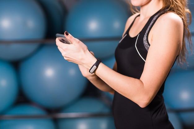 Primer plano de manos femeninas con rastreador de fitness y teléfono inteligente en el gimnasio