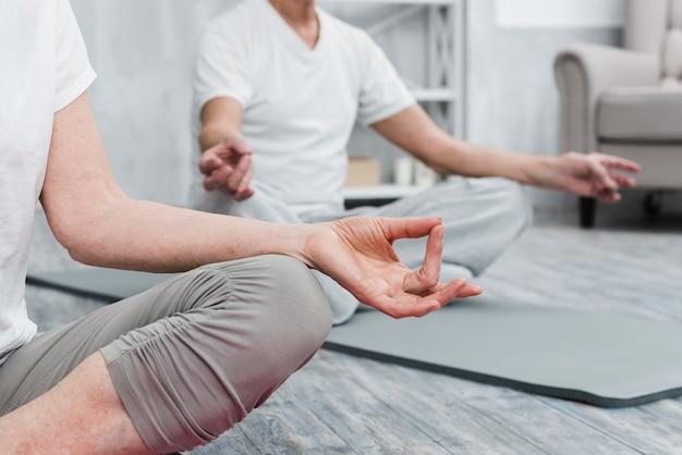 Primer plano de las manos de la gente trabajando en la alfombra de fitness