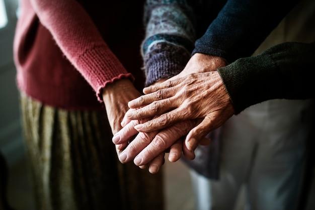 Primer plano de las manos del grupo de personas mayores