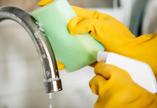 Primer plano de las manos con guantes limpiando el fregadero grifo tareas domésticas concepto