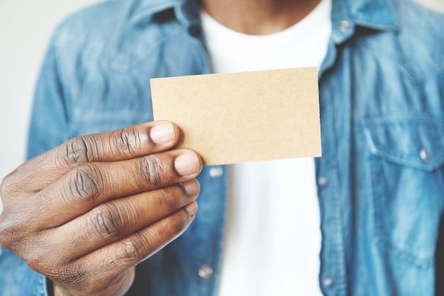 Primer plano de las manos del hombre africano sosteniendo la tarjeta de visita