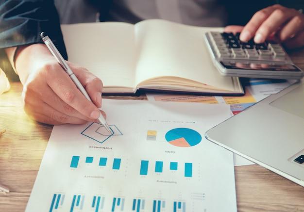 Primer plano de las manos del hombre de negocios que miran el documento del informe financiero