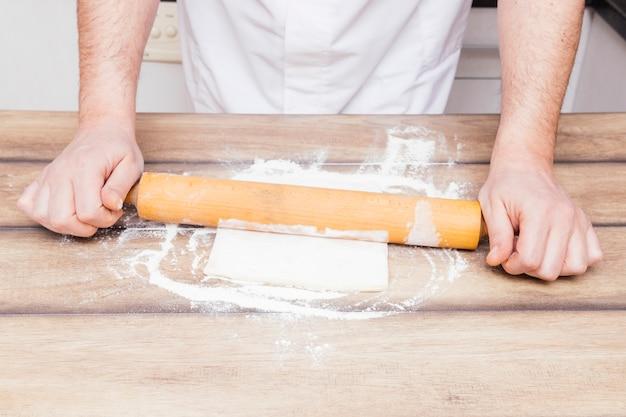 Primer plano de las manos de un hombre que desarrollan la masa en la mesa de la cocina