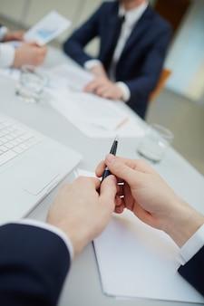 Primer plano de las manos de un hombre sosteniendo un bolígrafo