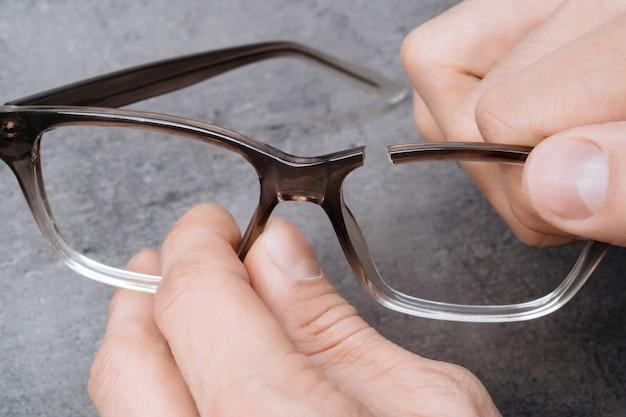 Primer plano de las manos del hombre sosteniendo un marco roto de gafas. optometrista joven sosteniendo en sus manos costillas de anteojos.
