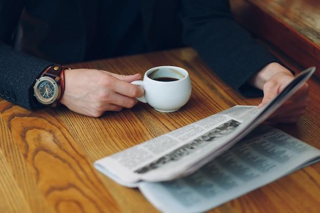 Primer plano de las manos del hombre sosteniendo una taza de café y un periódico