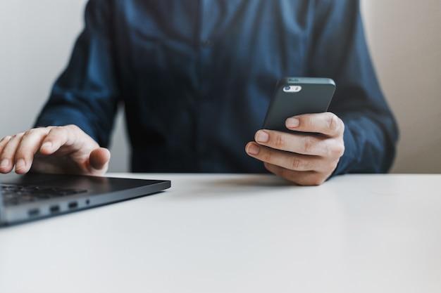 Primer plano de las manos del hombre sosteniendo el teléfono y escribiendo en un teclado de computadora portátil.