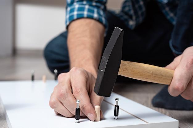 Primer plano de las manos de los hombres con un martillo recoge muebles de madera, montaje de estantes para el cofre