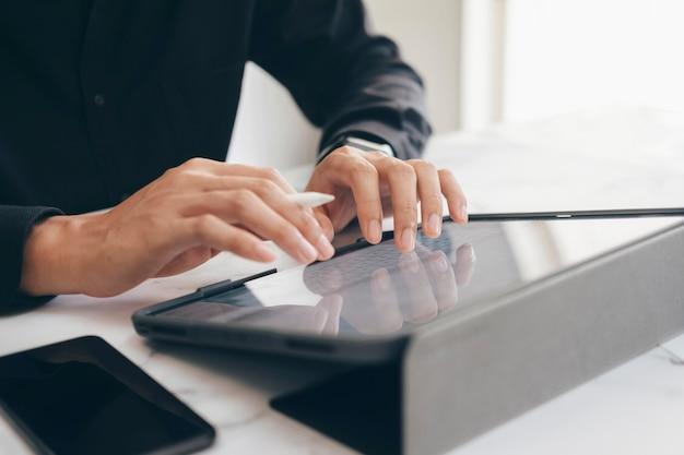 Primer plano de manos de joven empresario trabajando con tableta