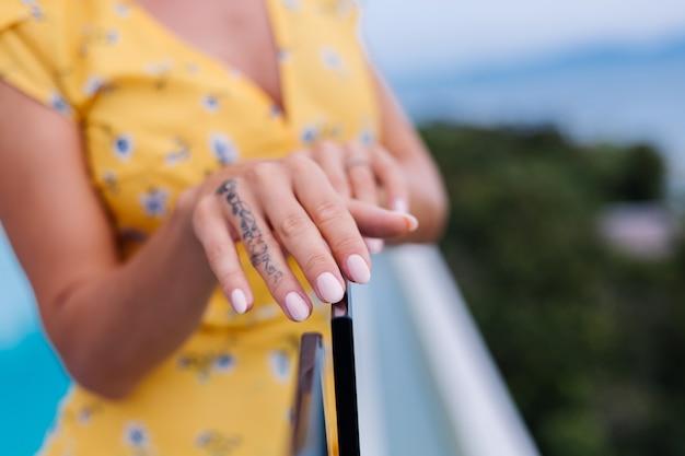 Primer plano de manos de manicura de mujer, con anillo en el dedo.