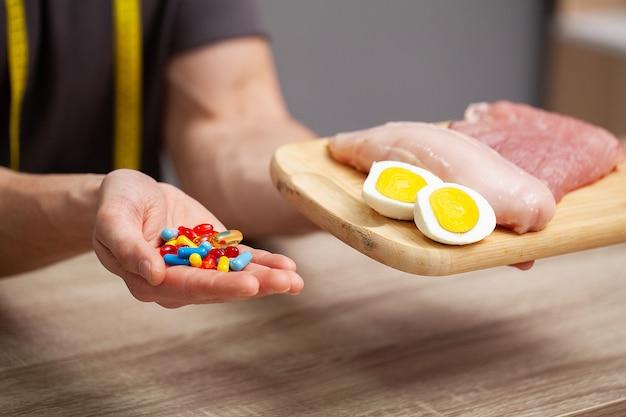 Primer plano de manos masculinas con alimentos ricos en proteínas en la tabla de cortar y la píldora en la mesa.