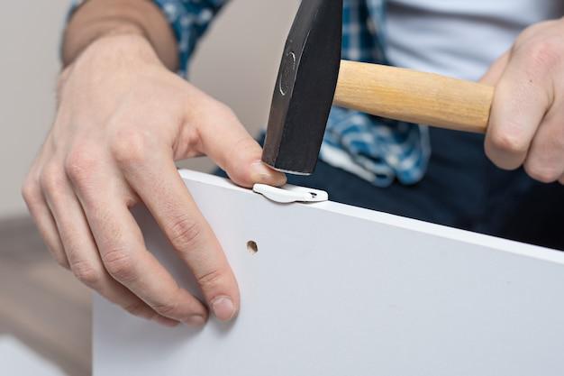 Primer plano de manos masculinas con martillo martillando clavos, golpe en el pulgar, lesiones, seguridad