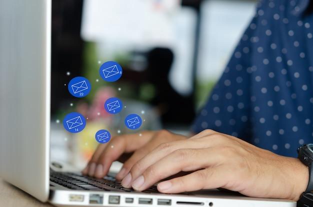 Primer plano de manos masculinas con teclado ordenador portátil con iconos de correo electrónico volador