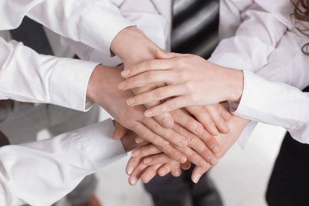Primer plano .las manos de los miembros del equipo empresarial juntas