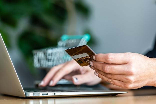 Primer plano de las manos de una mujer comprando en línea con una tarjeta de crédito y una computadora portátil, concepto de comercio electrónico