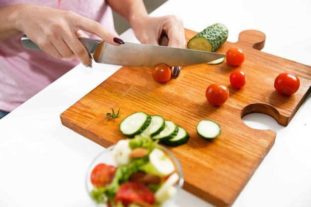Primer plano de manos de mujer cortar tomates en el tablero de madera