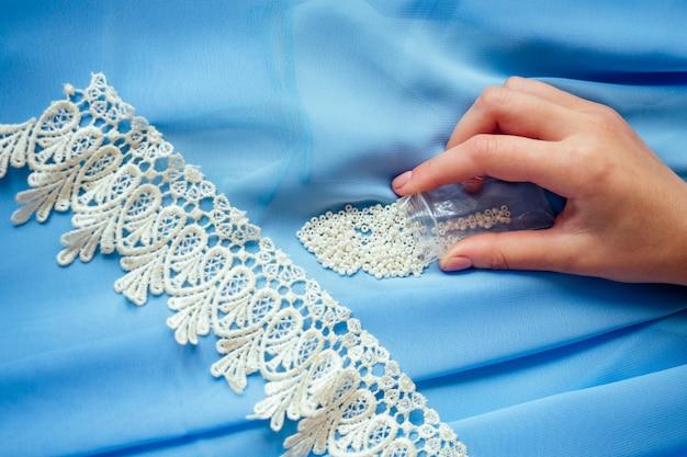 Primer plano de las manos de la mujer costurera sastre (modista) diseñador vestido de gasa azul cose perlas de encaje sobre un fondo azul en el estudio