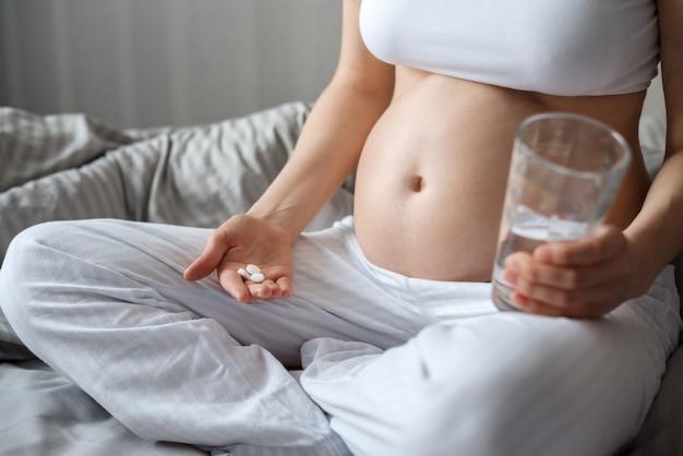Primer plano de las manos de la mujer embarazada con pastillas y vaso de agua.