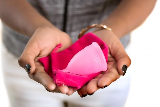 Primer plano de manos de mujer joven sosteniendo la copa menstrual, el concepto de ginecología, mostrando los pulgares para aprobar el uso de la copa menstrual