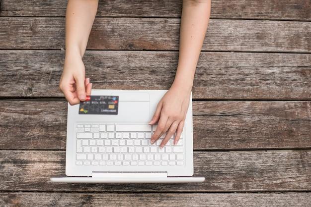 Primer plano de manos de mujer joven con tarjeta de crédito y utilizando equipo