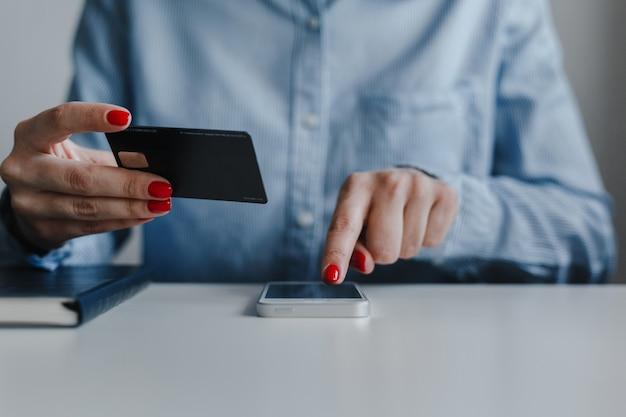 Primer plano de las manos de la mujer con uñas rojas sosteniendo la tarjeta de crédito y haciendo clic en el teléfono móvil para realizar el pago en línea