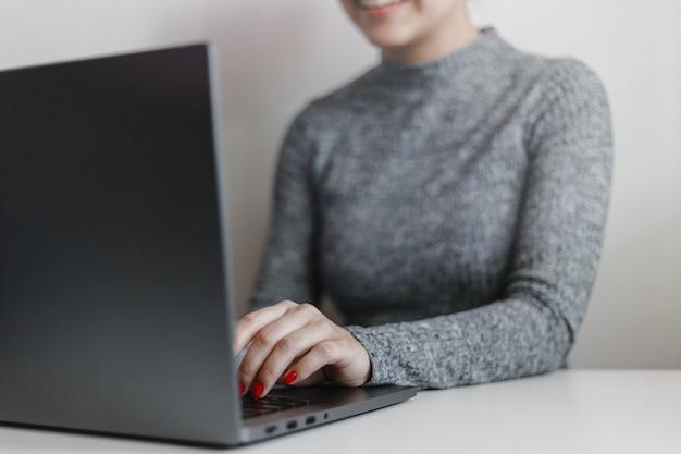 Primer plano de las manos de la mujer con uñas rojas en el teclado del portátil gris.