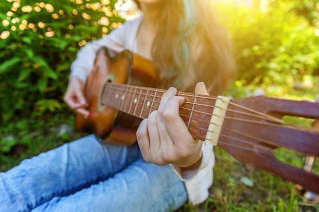 Primer plano de manos de mujer tocando guitarra acústica en parque o jardín