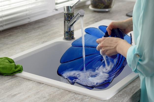 Primer plano de las manos de las mujeres para lavar platos, el concepto de las tareas domésticas
