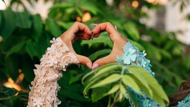 Primer plano de las manos de las mujeres que muestran en forma de corazón